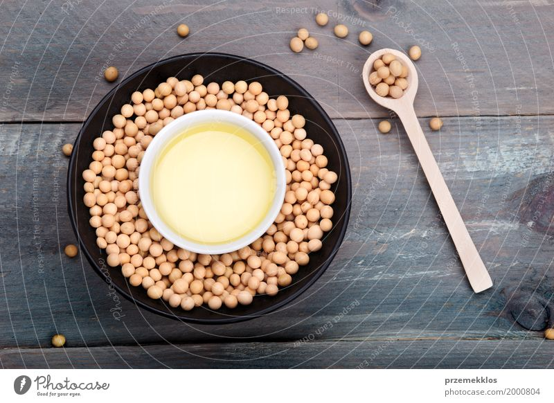 Soy beans and soy oil in bowls on wooden table Grain Nutrition Organic produce Vegetarian diet Bowl Spoon Wood Fresh Healthy Natural Beans Fiber food