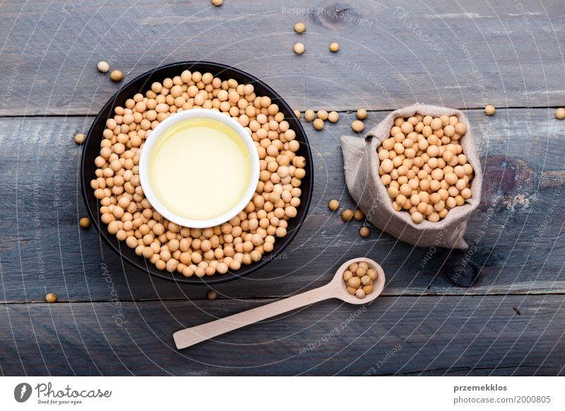 Soy beans and soy oil in bowls on wooden table Grain Nutrition Organic produce Vegetarian diet Asian Food Bowl Spoon Sack Container Wood Fresh Healthy Natural