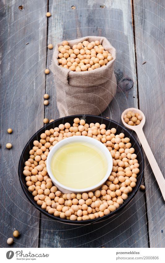 Soy beans and soy oil in bowls on wooden table Nutrition Organic produce Vegetarian diet Asian Food Bowl Spoon Container Wood Fresh Healthy Natural Beans Fiber
