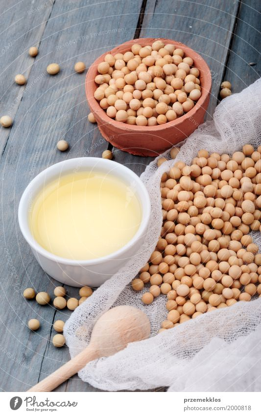 Soy beans and soy oil in bowls on wooden table Grain Nutrition Organic produce Vegetarian diet Bowl Spoon Nature Wood Fresh Natural Beans Fiber food healthy