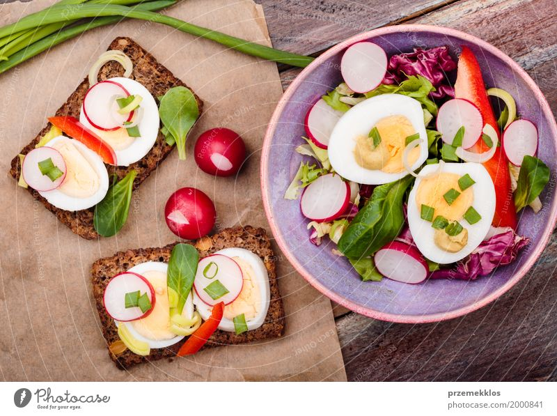 Healthy meal with eggs and vegetables Food Vegetable Lettuce Salad Bread Lunch Vegetarian diet Diet Bowl Table Wood Fresh Delicious Meal overhead Sandwich Sauce