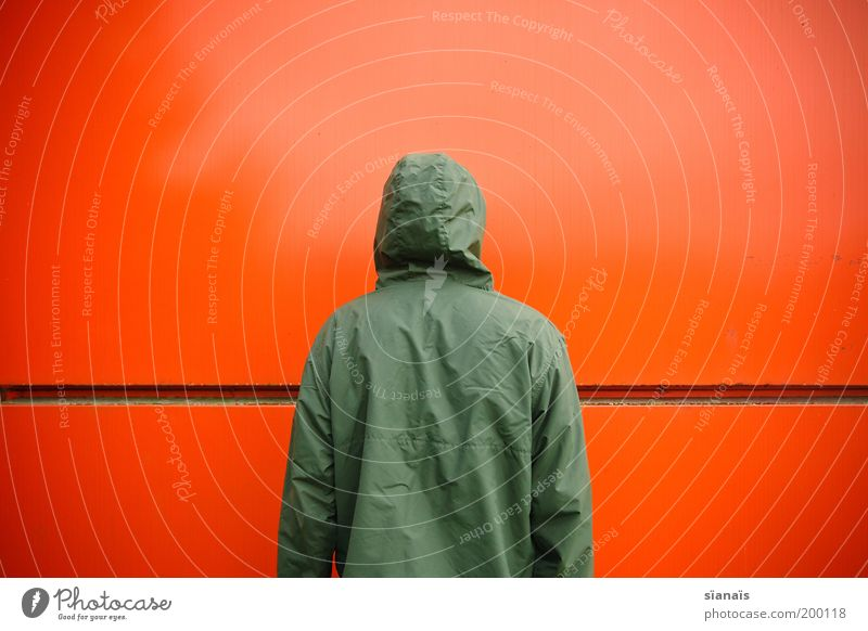 Human being Green Red Loneliness Wall (building) Wall (barrier) Orange Wait Masculine Back Facade Stand End Jacket Anonymous Timidity