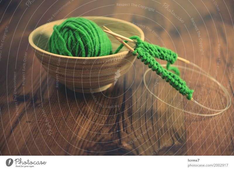 knitting with green wool in a bowl on wooden table. Design Leisure and hobbies Winter Warmth Fashion Wool Knit Creativity creased yarn craft Background picture