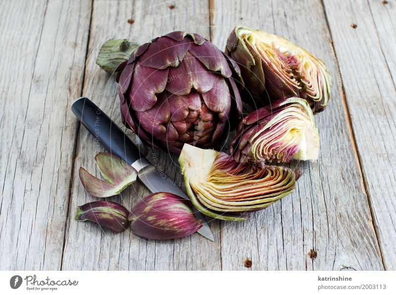 Roman Artichokes on a wooden board with knife Vegetable Nutrition Vegetarian diet Italian Food Knives Fresh Gray Green agriculture Purple cooking Cut Edible