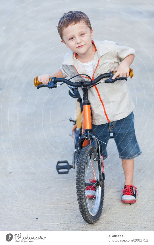 Happy little boy with bicycle standing on road Lifestyle Joy Relaxation Leisure and hobbies Adventure Summer Sports Cycling Child Human being Boy (child) Man