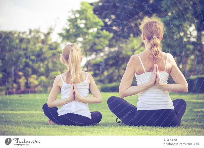 Mother and daughter doing yoga exercises on grass in the park Human being Child Woman Nature Summer Beautiful Relaxation Joy Girl Adults Lifestyle Sports Grass
