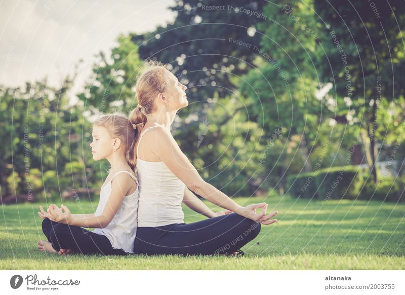 Mother and daughter doing yoga exercises on grass in the park at the day time Lifestyle Joy Happy Beautiful Body Wellness Harmonious Relaxation Meditation