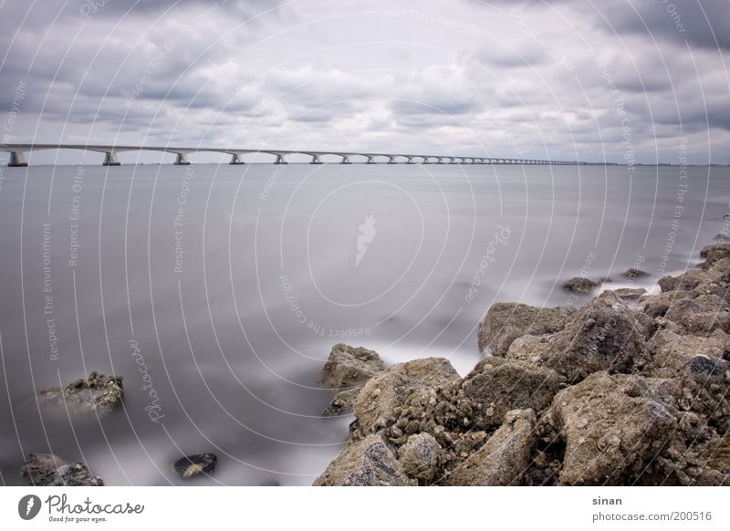 Coast with long bridge Landscape Earth Water Sky Clouds Autumn Wind Waves Bay North Sea Traffic infrastructure Bridge Exceptional Threat Fantastic Gloomy Blue