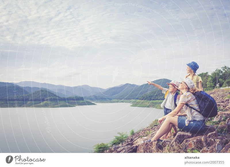 Happy family standing near the lake at the day time. Human being Child Woman Nature Vacation & Travel Man Summer Joy Mountain Adults Lifestyle Love Sports