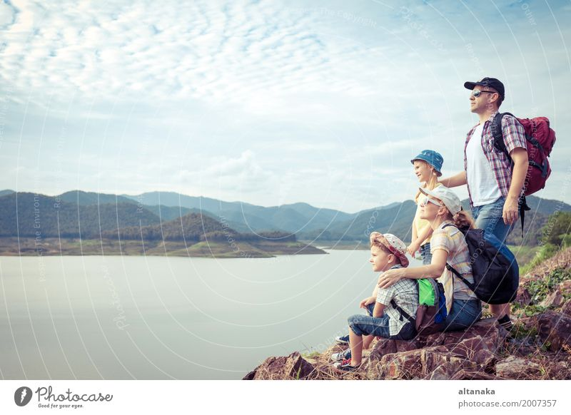 Happy family standing near the lake at the day time. Concept of friendly family. Lifestyle Joy Leisure and hobbies Vacation & Travel Trip Adventure Freedom