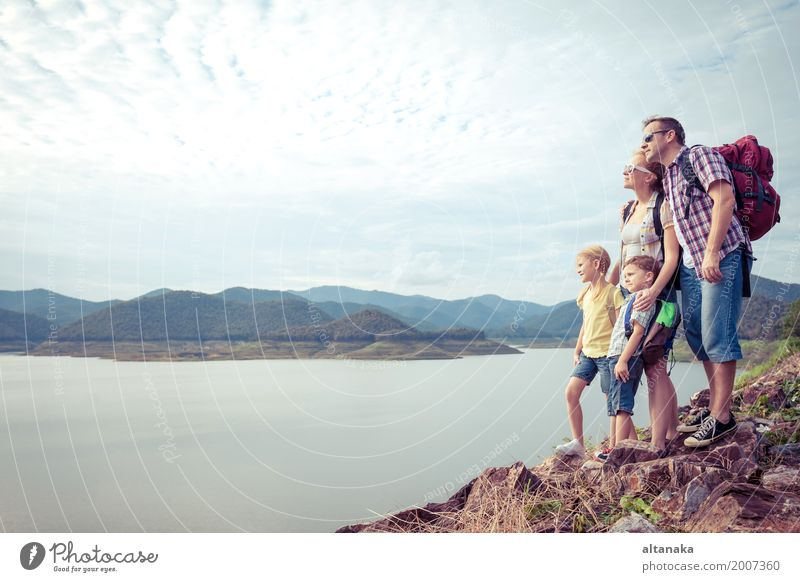 Happy family standing near the lake at the day time. Human being Child Nature Vacation & Travel Man Summer Joy Mountain Adults Lifestyle Love Sports Boy (child)