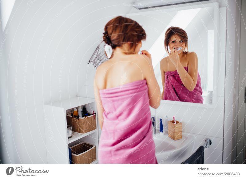Young happy woman brushing her teeth in bathroom Woman Youth (Young adults) Young woman 18 - 30 years Adults Lifestyle Healthy Feminine Happy Health care Pink Body Smiling Bathroom Teeth Mirror
