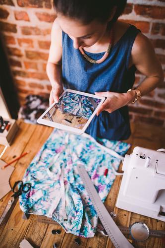 Young female blogger taking photo of dress with tablet Design Work and employment Profession Office Craft (trade) Business Screen Camera Sewing machine