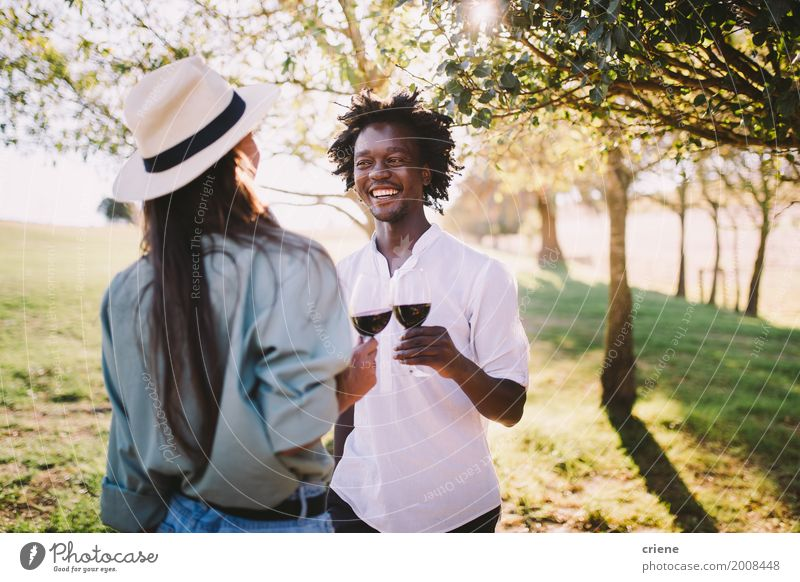 Mixed race couple having wine together on summer day Youth (Young adults) Young woman Summer Green Young man Joy Couple Together Friendship Park Smiling