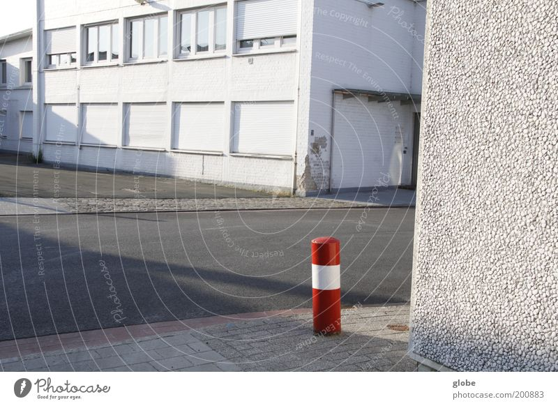 Urban Little Red Riding Hood Deserted Industrial plant Building Street Bollard Stand Loneliness White Structures and shapes Colour photo Exterior shot Day