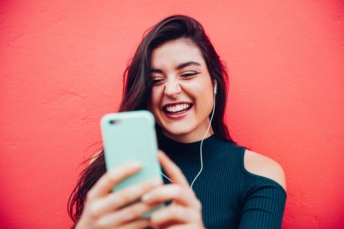 Young happy woman doing video call with smart phone Lifestyle Joy Music To talk Telephone Cellphone Technology Entertainment electronics Telecommunications