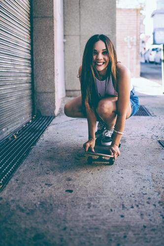 Happy female riding skate board in street Lifestyle Joy Leisure and hobbies Freedom Summer Sports Feminine Young woman Youth (Young adults) Woman Adults