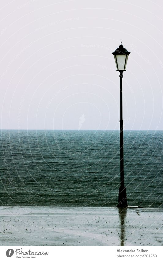 Is there a lantern... SECOND Climate Climate change Weather Bad weather Storm Wind Rain Waves Coast Lakeside Beach Ocean Cold Loneliness Wet Lantern Lamp post