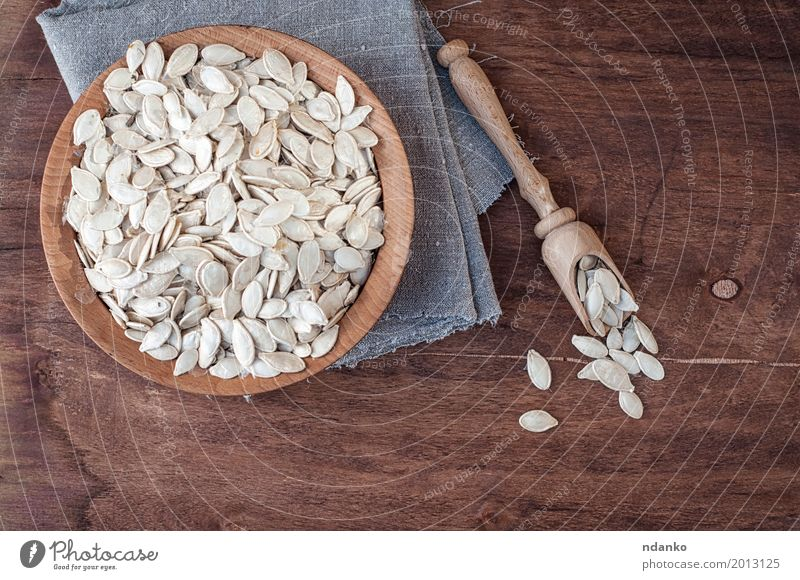 Unpeeled pumpkin seeds in a wooden bowl Vegetable Bowl Spoon Table Kitchen Wood Fresh Above Brown Gray White Snack Gourmet Top Tasty background board food Raw