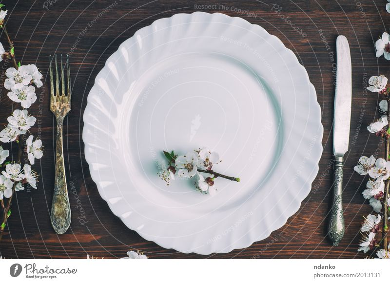 White plate with a fork and knife on a brown wooden surface Old Flower Dish Eating Wood Brown Above Metal Retro Vantage point Table Places Kitchen Restaurant