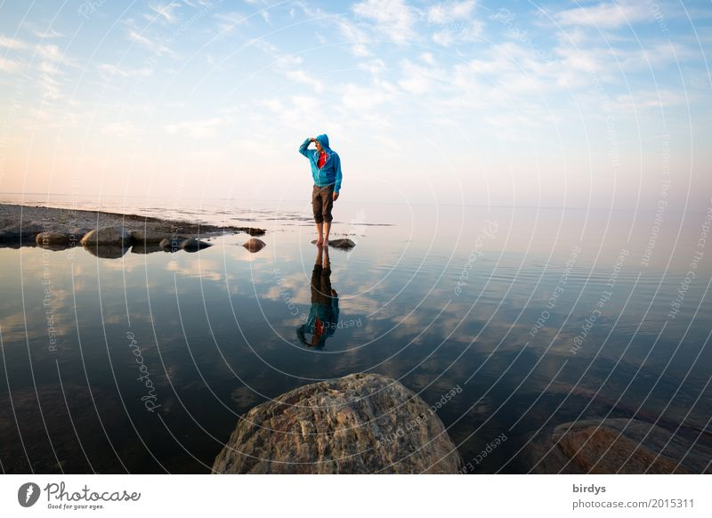 Man with turquoise hoody stands on a rock in the sea and looks into the distance Contentment Calm Masculine Adults 1 Human being 45 - 60 years Water Sky Horizon