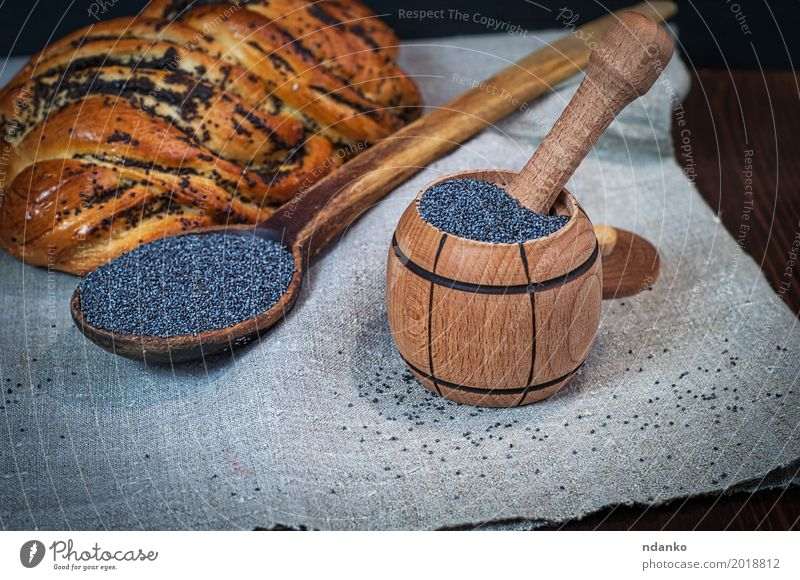 Poppy seeds in a wooden mortar Roll Dessert Herbs and spices Nutrition Bowl Spoon Wood Fresh Natural Brown Black rolls pastries Heap grain agriculture sweet