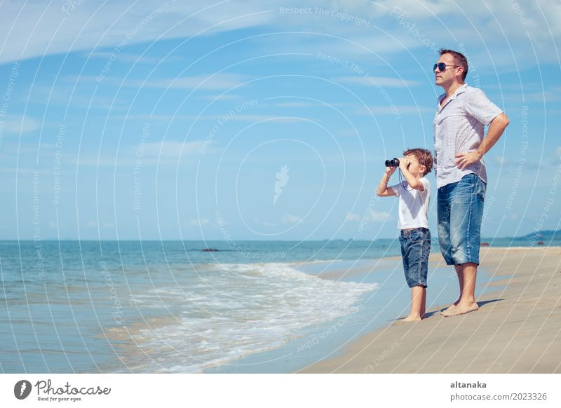 Father and son with binoculars standing on the beach at the day time. Concept of friendly family. Lifestyle Joy Relaxation Leisure and hobbies Playing