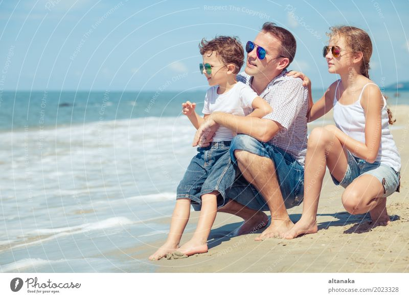 Father and children sitting on the beach at the day time. Concept of happy friendly family. Lifestyle Joy Relaxation Leisure and hobbies Playing