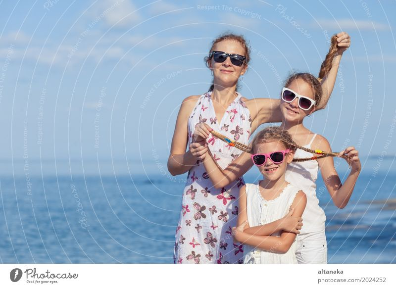 Mother and children playing on the beach at the day time. Concept of friendly family. Lifestyle Joy Relaxation Leisure and hobbies Playing Vacation & Travel