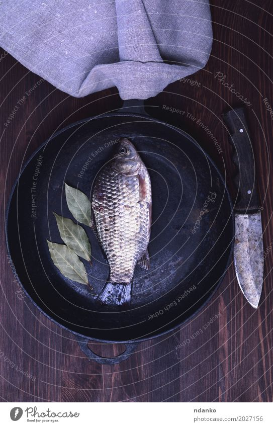 Fresh river carp in a black cast-iron frying pan Fish Herbs and spices Diet Pan Knives River Wood Eating Above Retro Brown crucian food cook Live vintage Edible