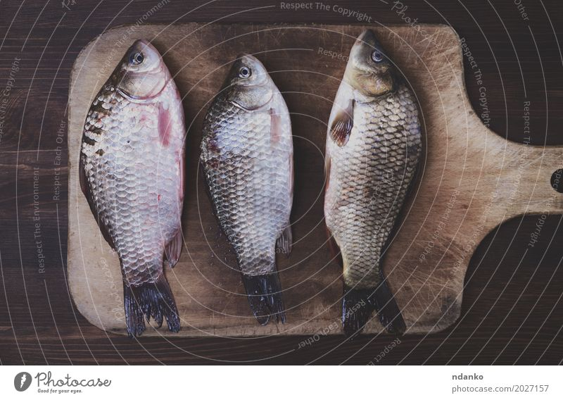 Three fresh river crucian on a kitchen board Fish Diet Wood Old Eating Retro Brown food three cook Live vintage Edible scales whole Tasty Top cooking
