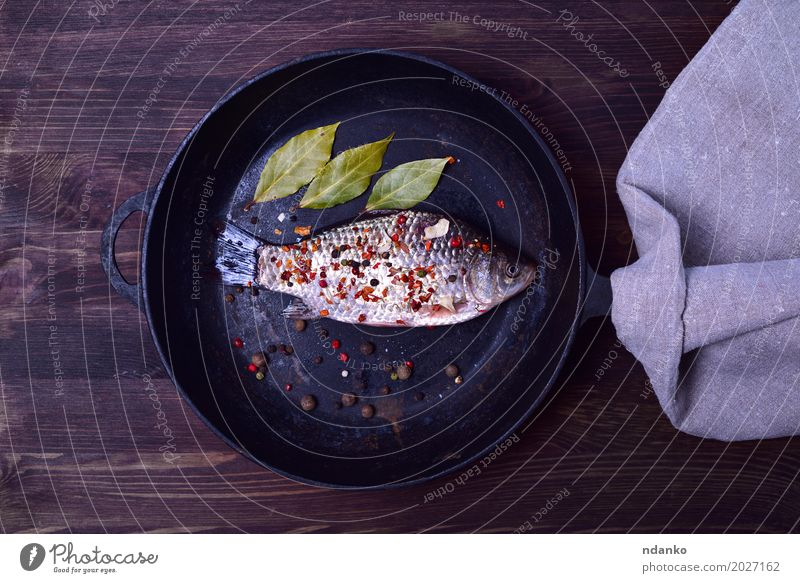 Crucian carp in spices on a black cast-iron frying pan Nature Green Leaf Black Eating Natural Wood Food Brown Above Nutrition Fresh Table Fish Herbs and spices Kitchen
