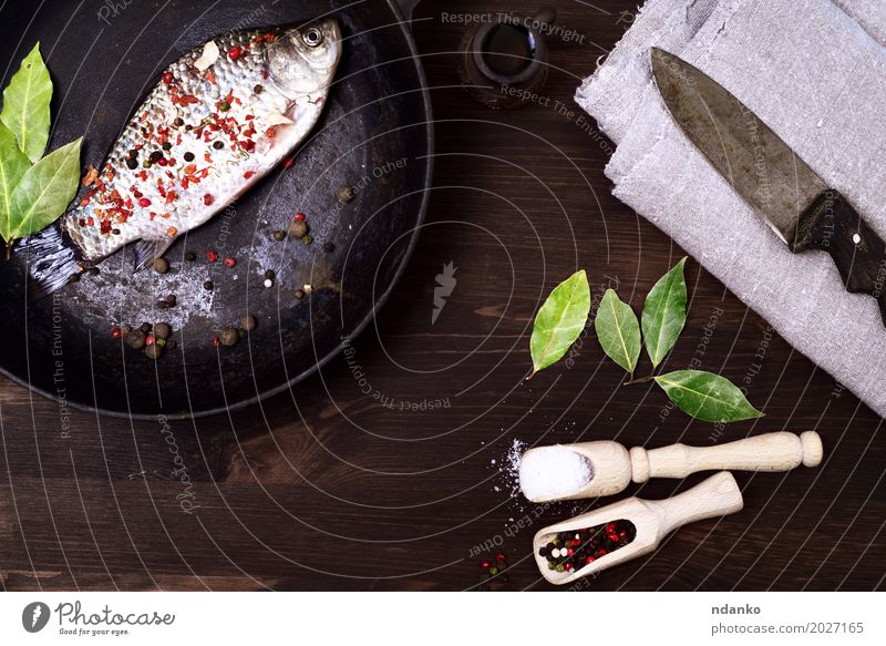 fish crucian in a cast-iron frying pan with spices Black Eating Brown Nutrition Fresh Retro Table Fish Herbs and spices Kitchen Delicious Top Spoon Pan Bay leaf