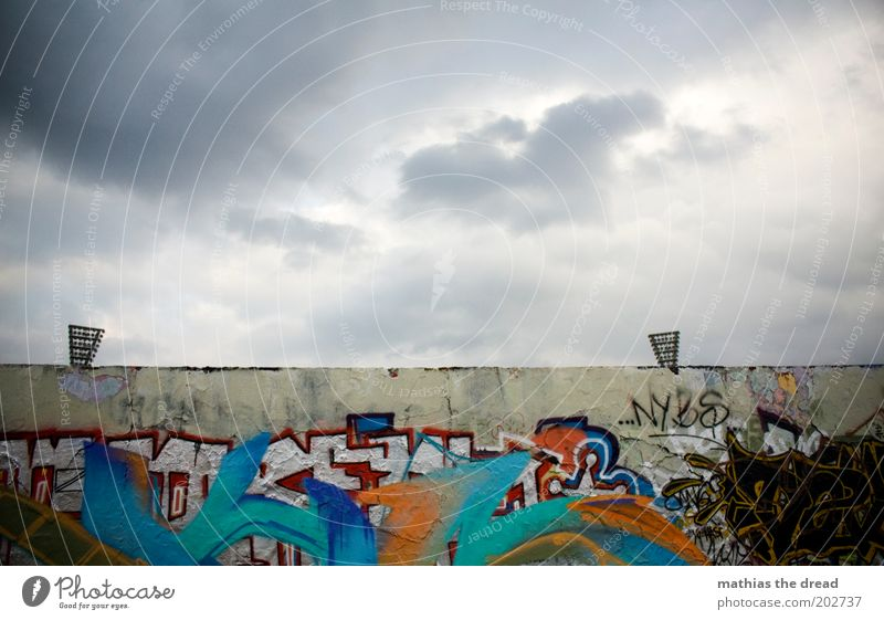 Sky City Clouds Dark Cold Wall (building) Wall (barrier) Building Graffiti Dirty Gloomy Characters Threat Sign Floodlight
