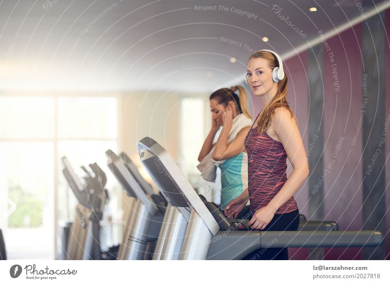 Attractive Woman with headphones on treadmill in the gym Lifestyle Happy Beautiful Face Leisure and hobbies Sports Adults 2 Human being 18 - 30 years