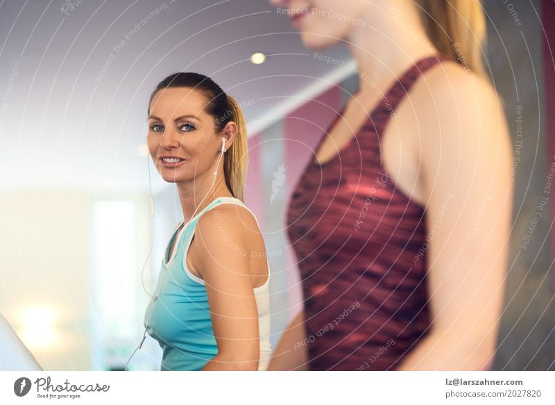 Attractive Woman with earphones on treadmill in the gym Lifestyle Happy Beautiful Face Leisure and hobbies Sports Adults 2 Human being 18 - 30 years