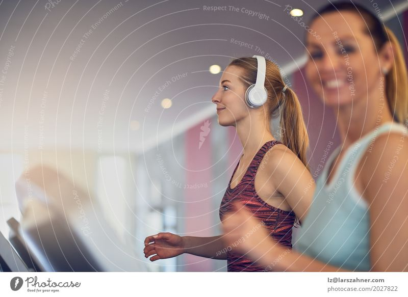 Attractive Woman with headphones on treadmill in the gym Human being Youth (Young adults) Beautiful 18 - 30 years Face Adults Lifestyle Sports Happy Copy Space