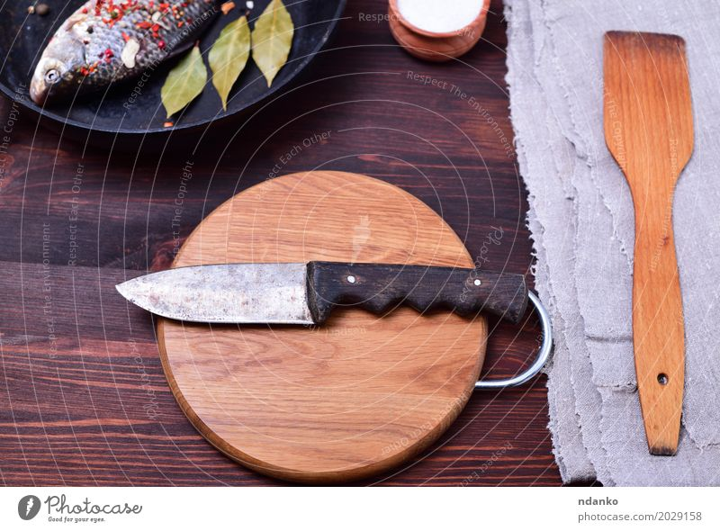 Kitchen knife on a circular cutting wooden board Fish Eating Pan Knives Table Old Retro Brown Gray Black Knife Top Carp spatula napkin cook frying pan food