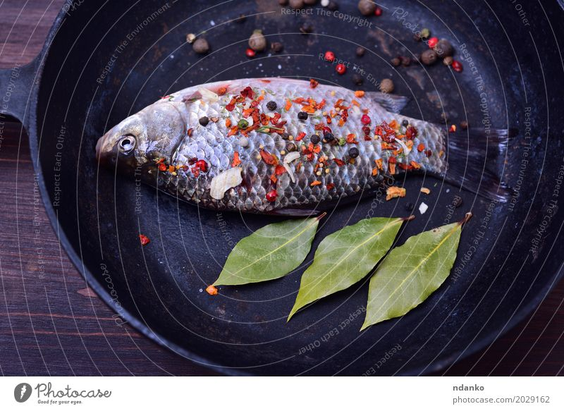 Carp with spices in a black cast-iron frying pan Fish Herbs and spices Pan Table Kitchen Nature Leaf Wood Eating Fresh Above Brown Green Black crucian pepper