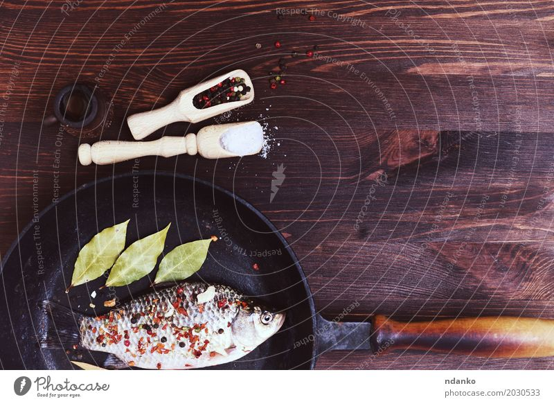 fish carp with spices in a black cast-iron frying pan Nature Leaf Black Eating Natural Wood Food Brown Above Fresh Table Fish Herbs and spices Kitchen Top Diet
