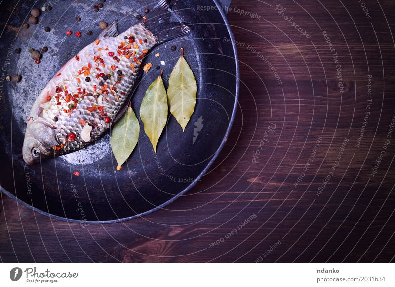 Carp with spices in a black cast-iron frying pan Green Black Eating Wood Food Brown Above Nutrition Fresh Table Fish Herbs and spices Kitchen Top Diet Raw