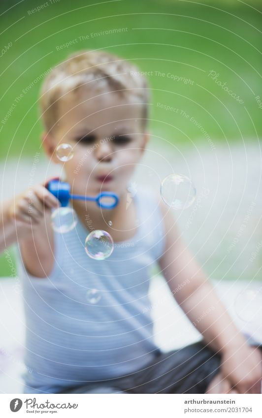 Boy blowing soap bubbles in the meadow Leisure and hobbies Playing Vacation & Travel Trip Summer vacation Garden Human being Masculine Child Boy (child) Infancy