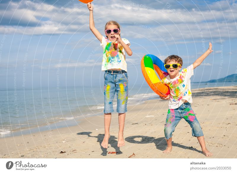 Happy children playing on the beach Human being Child Nature Vacation & Travel Summer Beautiful Sun Hand Ocean Relaxation Joy Beach Lifestyle Emotions Sports