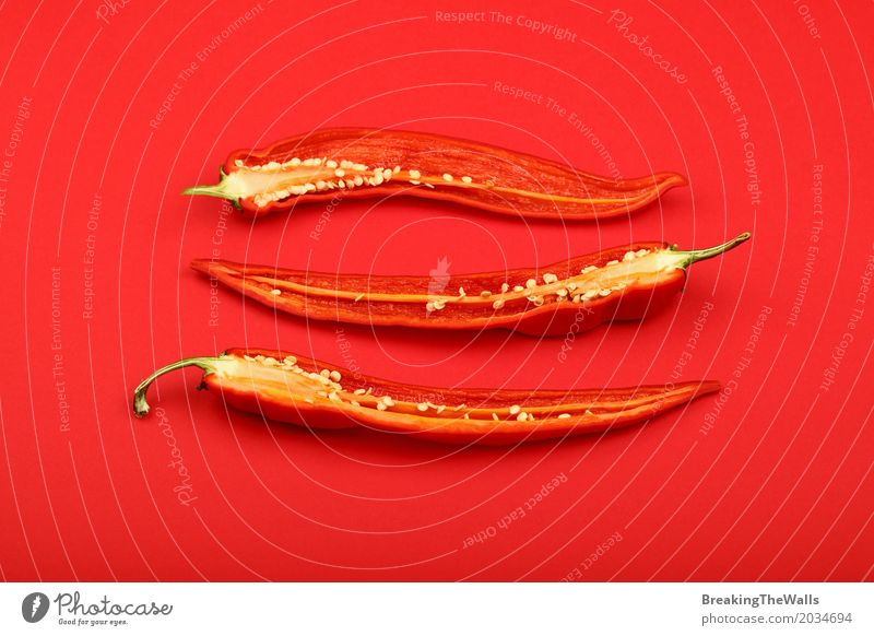 Three halved fresh hot chili peppers over red Colour Red Art Food Nutrition Fresh Vantage point Idea Paper Herbs and spices Cooking Vegetable Hot Slice