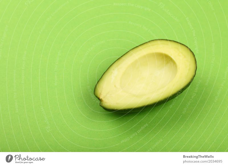Fresh avocado half on green paper background Colour Green Healthy Eating Natural Food Nutrition Vantage point Paper Vegetable Organic produce Top Slice