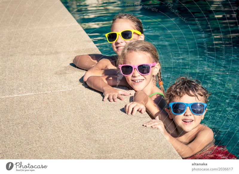 Three happy children playing on the swimming pool Lifestyle Joy Happy Face Relaxation Swimming pool Leisure and hobbies Playing Vacation & Travel Summer Sun