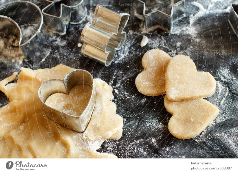 Close up of cookie cutters in a dough on a dark table Heart Kitchen Dessert Make Baked goods Dough Raw Flour Bakery Preparation Baking Rolling pin Home-made
