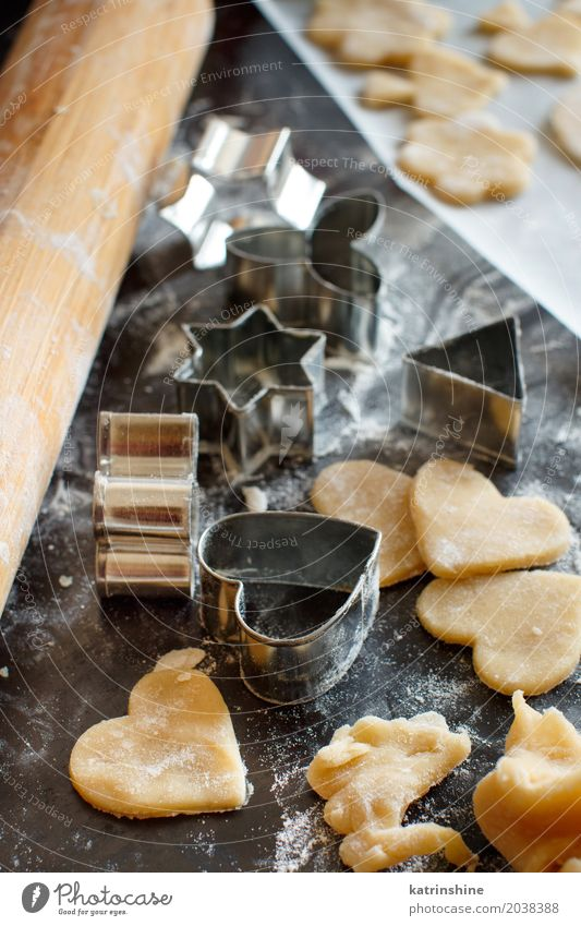 Close up of cookie cutters and rolling pin on a dark table Heart Kitchen Dessert Make Baked goods Dough Raw Flour Bakery Preparation Baking Rolling pin