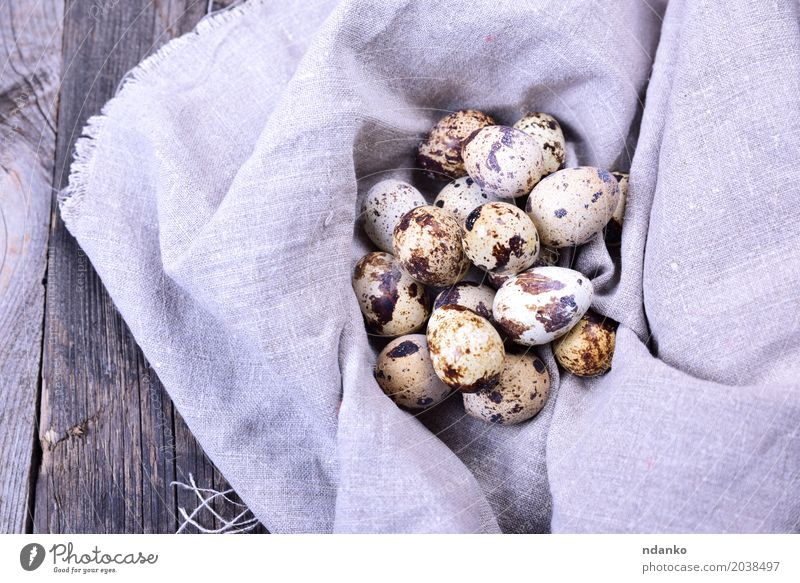 Group of quail eggs in a gray textile napkin Eating Natural Wood Small Gray Brown Above Fresh Table Easter Farm Breakfast Tradition Diet Consistency Rustic