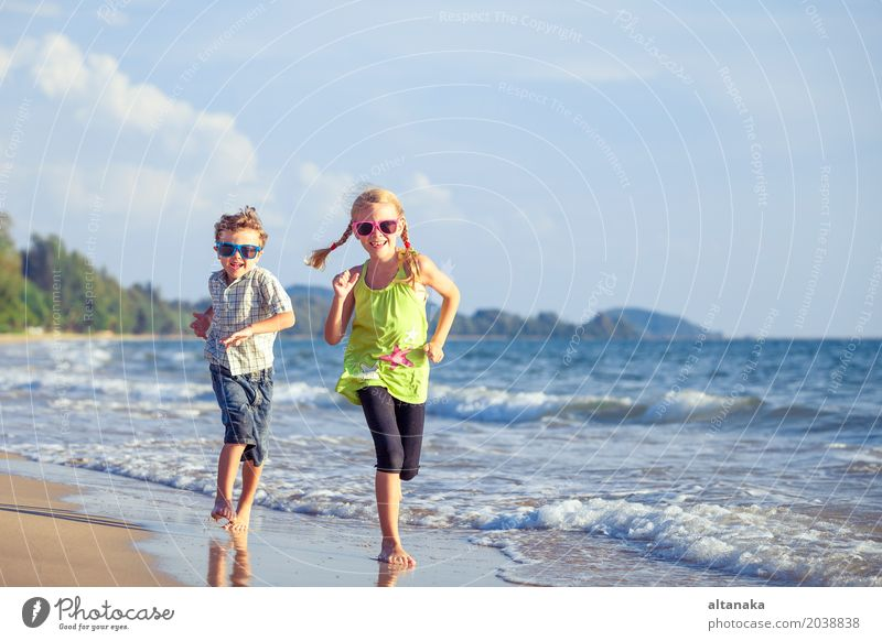 Happy children playing on the beach at the day time. Human being Child Nature Vacation & Travel Summer Sun Hand Ocean Relaxation Joy Beach Lifestyle Emotions